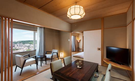 Tatami Styled Family Suite Living Area With TV, Seating for Four at Dining Table, Two Armchairs and Coffee Table By Window With Open Drapes, and Open Doorway to Bedroom