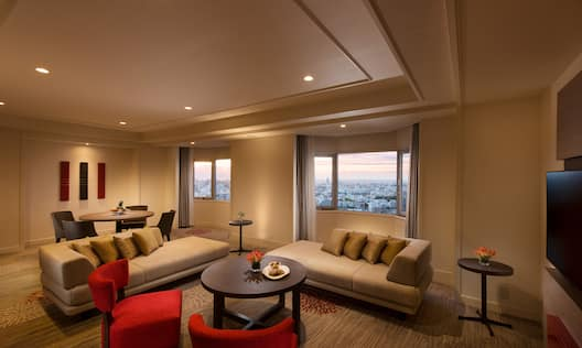TV, Tables, Sofas. Red Chairs, Wall Art, Seating for Four at Dining Table, and Windows With Open Drapes to City View in Suite Living Area
