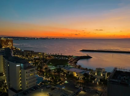an overhead view of hotel surrounding buildings and the ocean