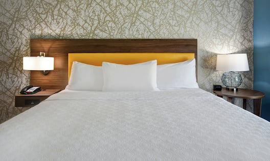 Large bed with side tables and lamps.