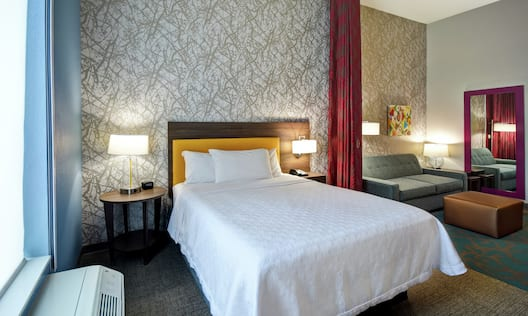 Large bed with side tables, lamps and couch seating area.