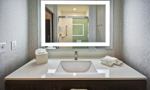 Guest bathroom vanity with sink and mirror.