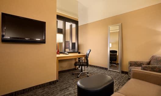 Armchair, Sofa, Ottoman, TV, Work Desk With Illuminated Lamp, Ergonomic Lamp, and Full Length Mirror in Junior Suite Living Area