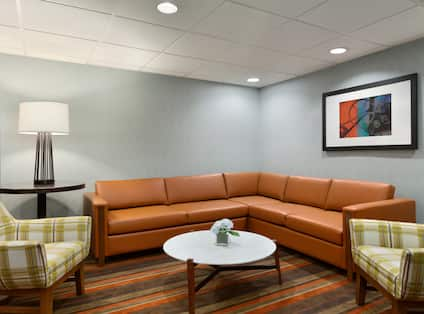 Suite Living Room With Sectional Sofa, Chairs, Wall Art, Tables, and Illuminated Lamp