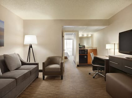 Suite Lounge Area and With Microwave and Mini Fridge at Hospitality Center, Ergonomic Chair at Work Desk, TV, Wall Art Above Sofa, Illuminated Floor Lamp, Armchair, and View Into Bedroom