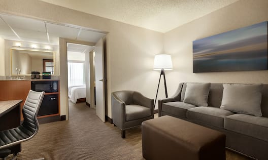 Suite Lounge Area and With Ergonomic Chair at Work Desk, Hospitality Center, View Into Bedroom With Two Double Beds, Armchair, Illuminated Lamp, Wall Art Above Sofa, and Ottoman