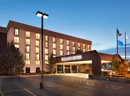 Illuminated Hotel Exterior, Signage, Parking Lot and Entry at Night