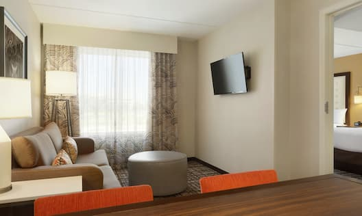 Guestroom Suite Living Area with Sofa, Footrest, Wall Mounted HDTV and Dining Table