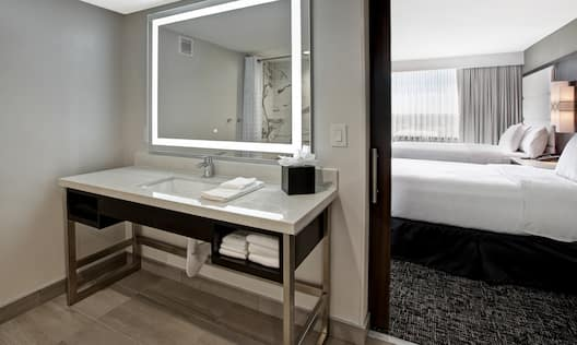 guest room with bathroom vanity and two beds