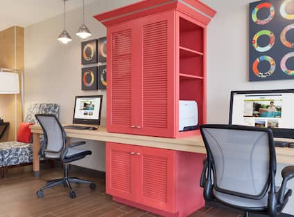 Floor Lamp, Lounger Chair, Wall Art, Red Storage Cabinet With Printer Between Two Computers on Long Desk, Two Black Ergonomic Chairs in Business Service Area