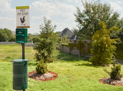 """""""Pet Pit Stop"""" Sign Above Waste Bag Dispenser by Trees and Grass Area in Pet Area"""