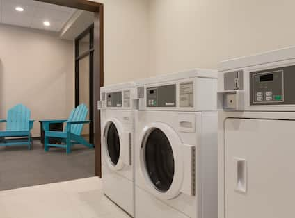 Open Doorway to View of Two Blue Chairs, Spin2 Cycle Laundry Room With Coin Operated Washing and Drying Machines