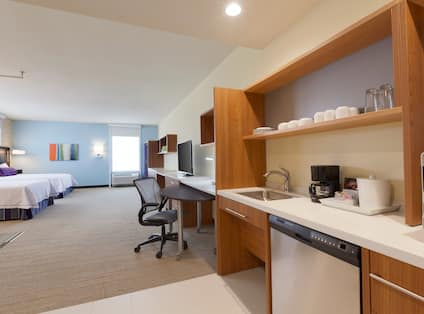 Kitchen With Dinnerware in Wood Cabinets, Sink, Dishwasher, and Microwave, Work Desk, TV, Window, Illuminated Lamps, Wall Art, Two Queen Beds With Lamp on Bedside Table in Accessible Studio Suite