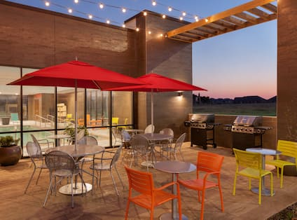 Illuminated Outdoor Patio With Chairs, Tables With Red Umbrellas, and Two Barbecue Grills at Night