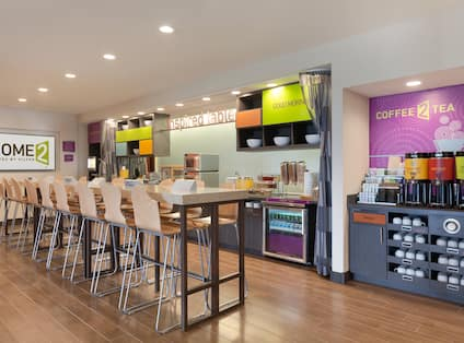 Counter Seating, TV, Signage Above Food Service Area and Hot Beverages in Dining Area