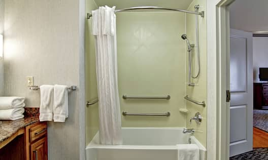 Fresh Towels on Counter by  Accessible Bathtub With Grab Bars and Handheld Showerhead