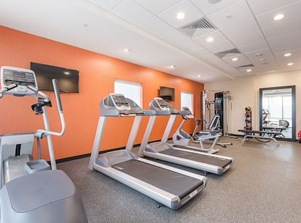 Fitness Center With Cardio Equipment, TVs, Weight Machine in Corner, Weight Balls, Weight Bench, , Large Mirror, and Red Exercise Ball