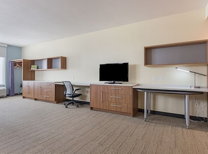 Accessible Studio Suite With Dining Table, HDTV, Work Desk, and Draped Closet by Window