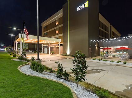 Angled View of Illuminated Exterior Entrance, Driveway, Flagpole, Landscaping, Signage, and Patio at Night