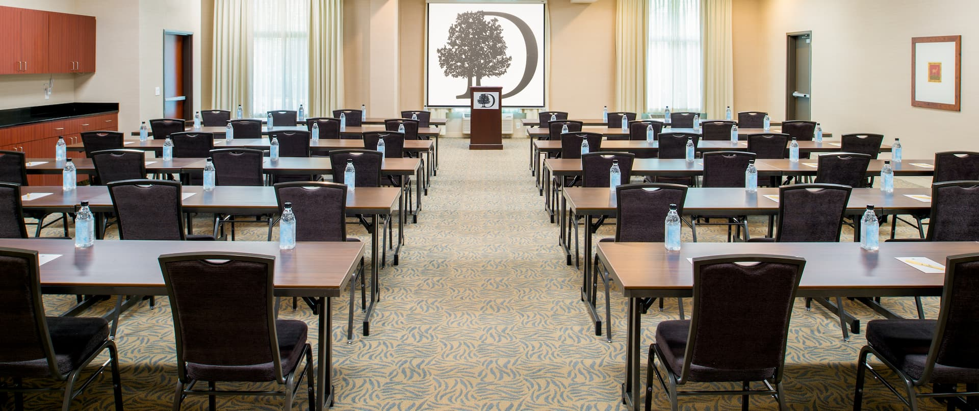 Classroom Setup in Meeting Room With Tables and Chairs Facing Windows With Sheer Drapes, Presentation Screen and Podium