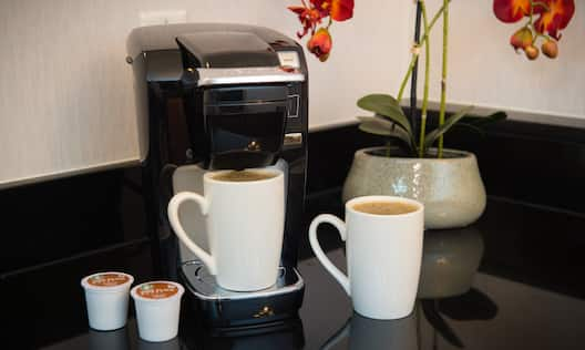 Hospitality Center With Coffeemaker, Mugs, and Flowers in Suite