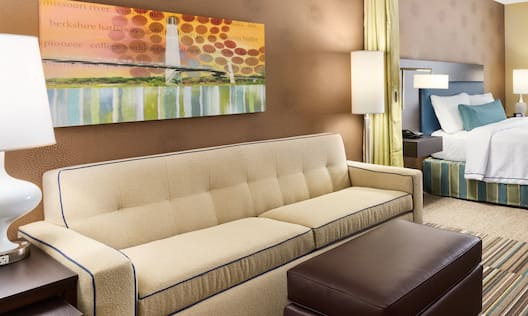 Guestroom Suite with King Bed, Lounge Area, and Room Technology
