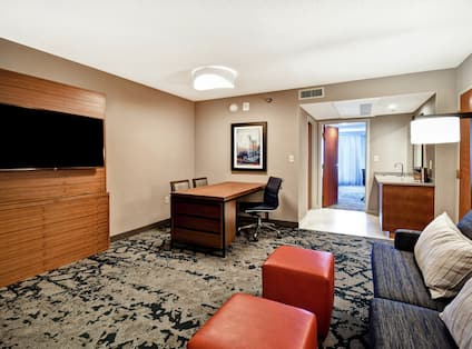 Living area in suite with workdesk and tv