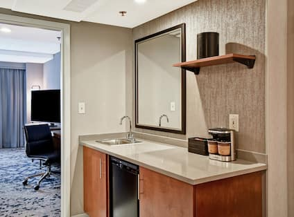 Wetbar in room with mirror and sink