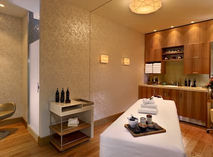 Spa Treatment Room With Chairs, Massage Table, Sinks and Fresh Towels in Wood Cabinet
