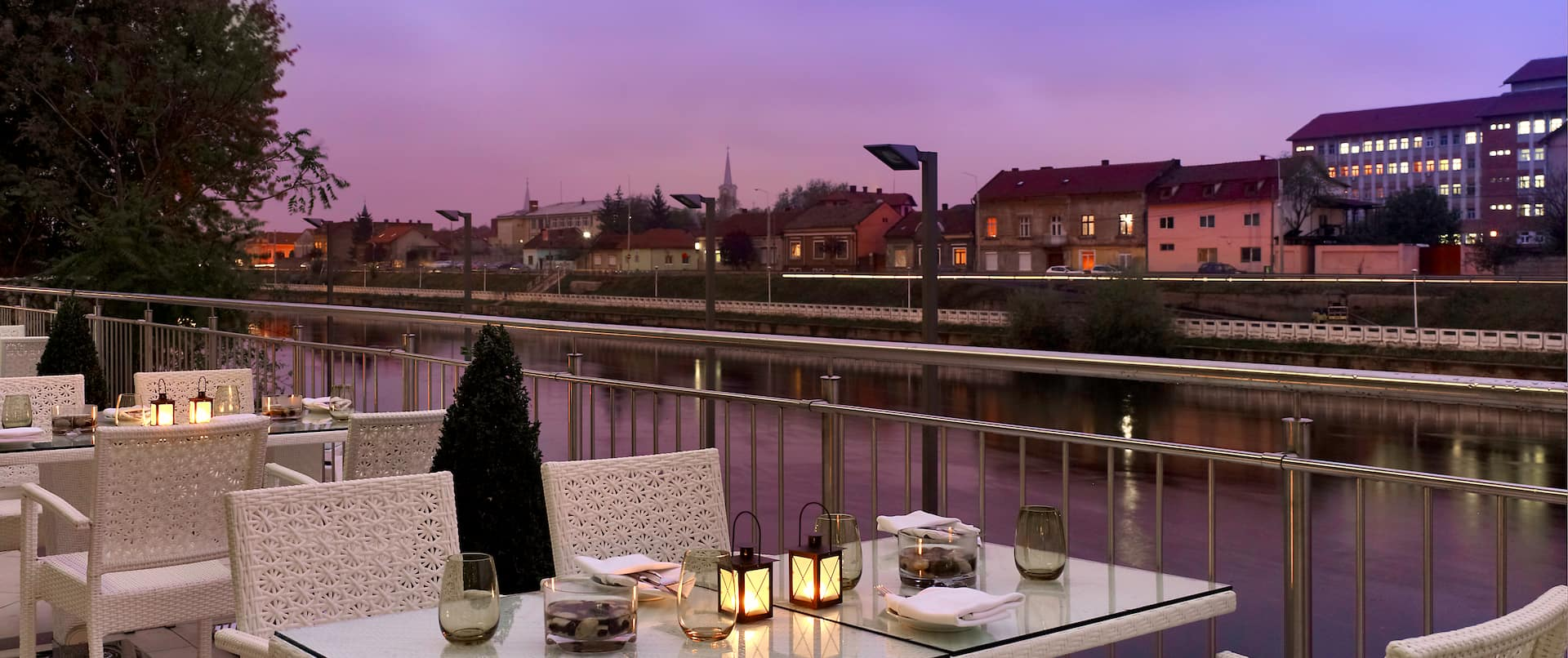 Laurus Restaurant Patio Dining Tables With Place Settings, Candles, White Chairs, and View of Illuminated City at Night