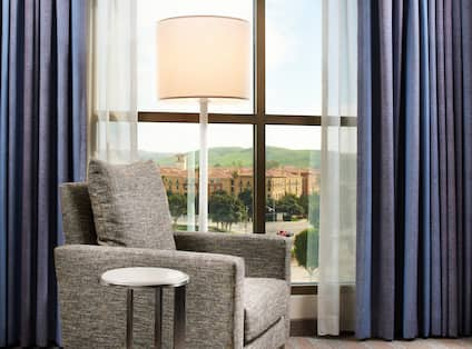 Detailed View of Side Table, Armchair, and Illuminated Floor Lamp by Window With Open Drapes to City View in Guest Room