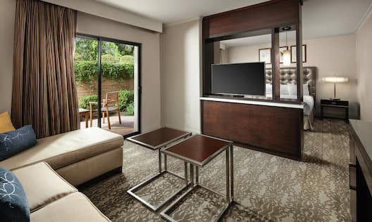 a suite living area with a tv and half wall room divider