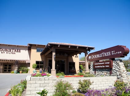 Daytime View of Hotel Exterior, Signage, Landscaping, Porte Cochere, and Entrance