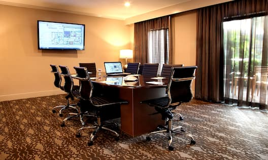TV, Illuminated Lamp, Windows With Sheer Drapes, and Seating for 8 at Boardroom Table With Laptop Computer and Notepads in Meeting Room Suite