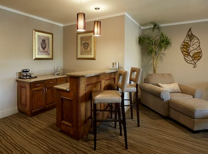 Wetbar Area With Wall Art, Coffee Maker, Counter Seating, Armchair and Ottoman in Suite