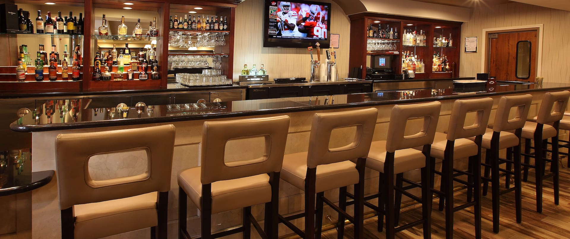 Angled View of Counter Seating and TV at Fully Stocked Bar