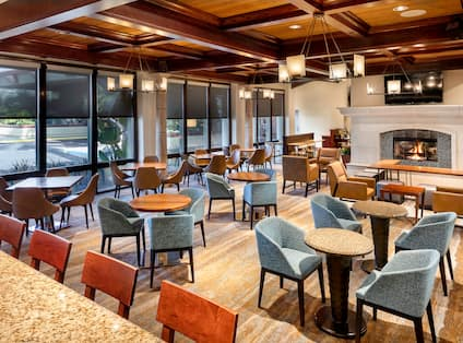 Vineyards Restaurant Dining Room Area With Tables, Mixed Seating, Large Windows, and TV Above Fireplace