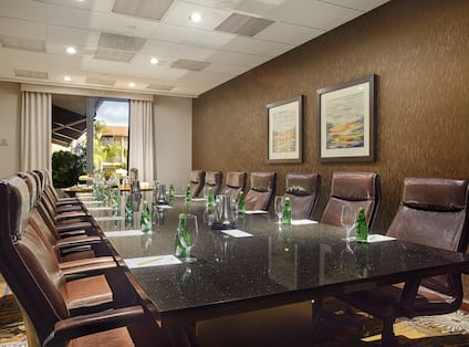 Wall Art, Window With Open Drapes, and Seating for 14 at Boardroom Table With Drinking Glasses and Bottled Water