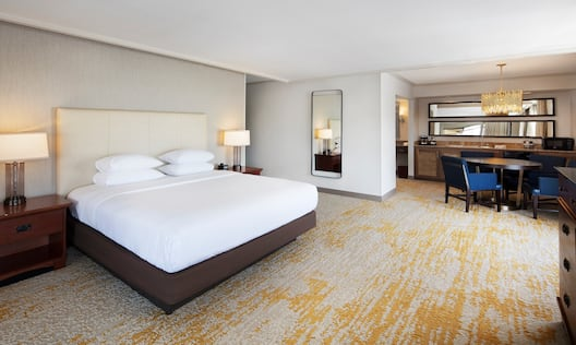 King Bed Between Two Illuminated Lamps on Bedside Tables, Full Length Mirror, Open Door to Bathroom, Wall Mirrors Above Wet Bar, and Seating for Four at Round Dining Table in Suite