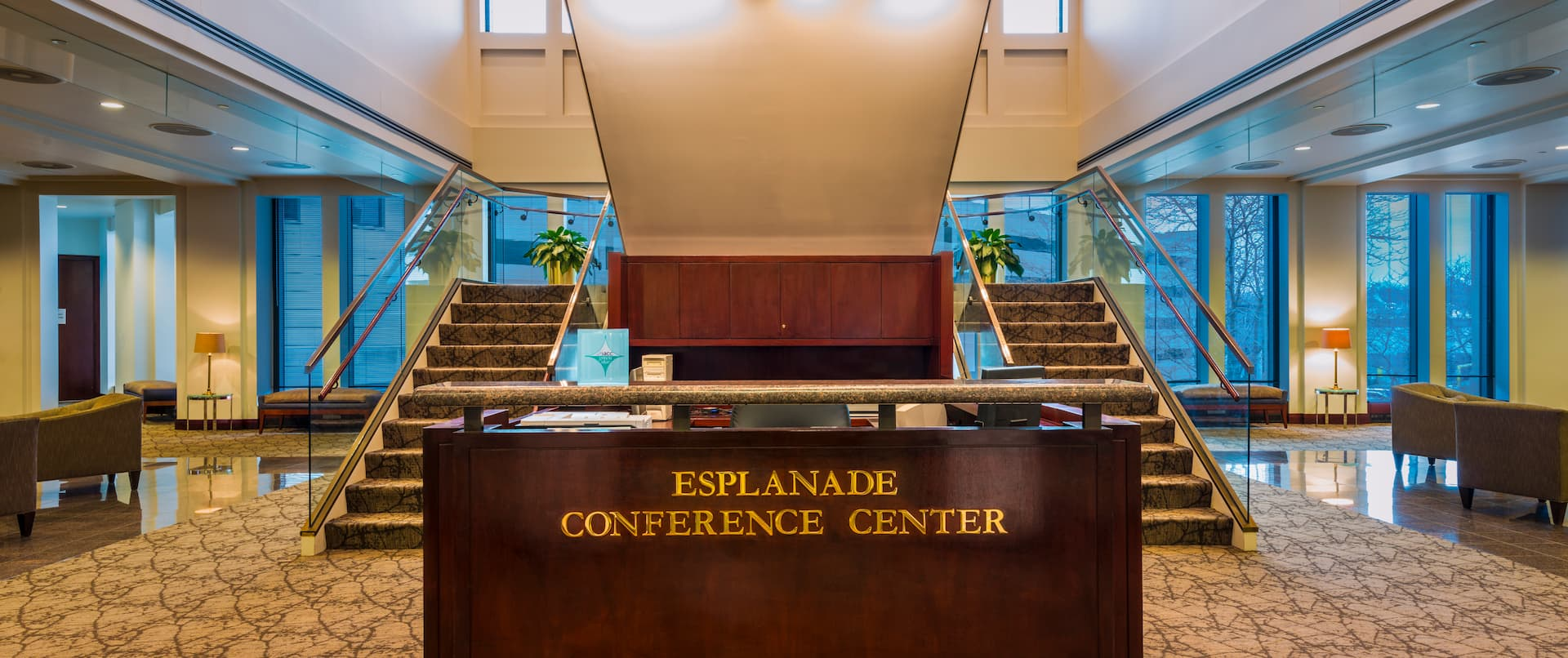 Esplanade Conference Center Signage on Reception Desk With View of Double Staircases, Soft Seating, and Windows in Background