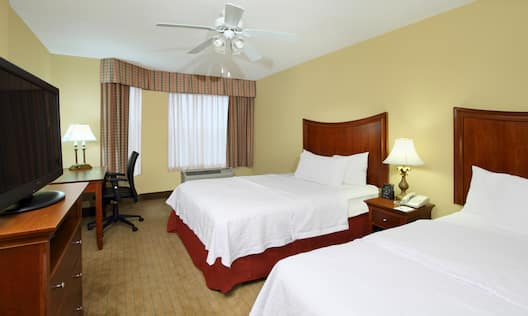 Two Queen Beds, Bedside Table With Lamp, Ceiling Fan, TV and Work Desk in Corner by Window