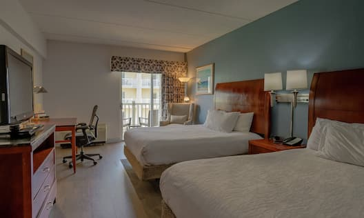 Double Queen Guestroom Bedroom with Two Beds, Room Technology, Work Desk, Lounge Area, and Outside View
