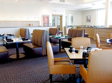 Napkins and Drinking Glasses on Dining Tables, Booths, Chairs, Large Windows, Glass Door and View of Food Service Area Behind Partition in Nectar Restaurant & Bar