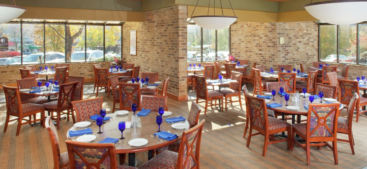 White Plates, Blue Drinking Glasses and Blue Napkins on Dining Tables, Chairs, and Large Windows in Burchfield's Restaurant