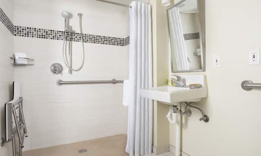 Studio Roll-in Shower with Accessible Sink, Folded Shower Chair, Detachable Shower Head, and Grab Bars