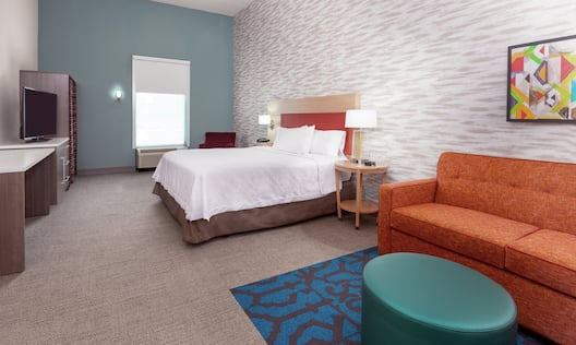 Accessible King Suite with Bed, Lounge Area, and Room Technology.