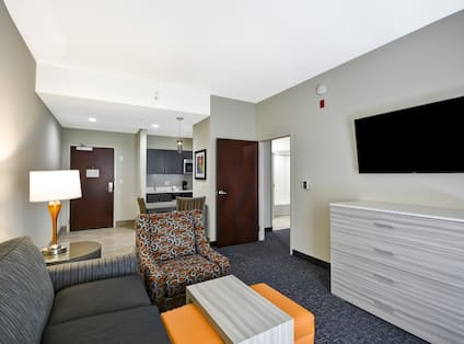 Homewood Suites by Hilton Orlando Theme Parks - Living Room with Sofa, Dresser, TV, Chair and Tables