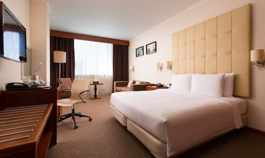 Queen Bed, Lamps Above Bedside Table, TV, Work Desk With View of Soft Seating, Table, Window With Long Drapes, and Wall Art in Living Area of Junior Suite