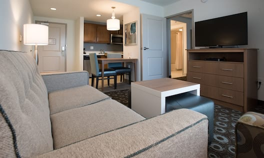 One Bedroom Living Room with Kitchen, dining table, lounge sofa, footrest, TV, and room entrance