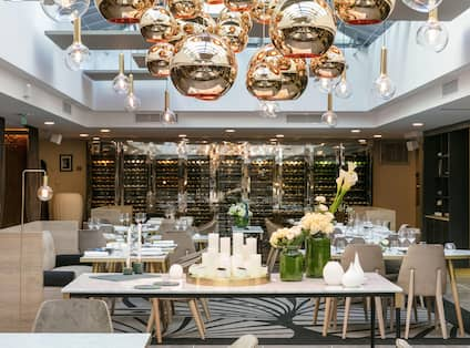La Verriere Restaurant Seating with Flowers and Candles plus Large Reflective Gold Balls Suspended from Ceiling